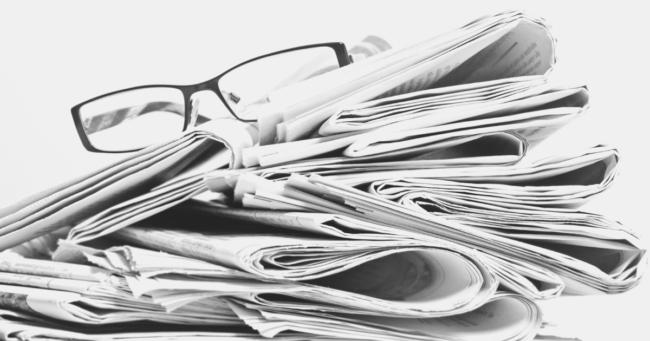 giornali ammucchiati in modo disordinato con sopra un paio di occhiali