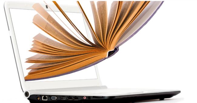 libro aperto che sta planando su computer portatile