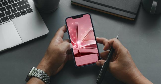 mani che reggono smartphone con immagine libro aperto