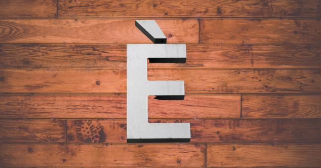 lettera e accentata su sfondo legno