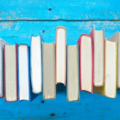 fila di libri si sfondo azzurro