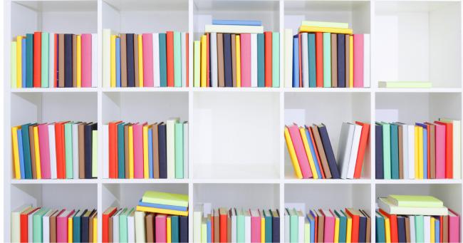 libreria bianca con sistemazione di libri con dorsi colorati